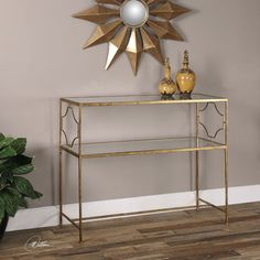 """This console table by Uttermost is an upscale, traditional design in gold-leafed iron with moderate antiquing. The top and gallery shelf are made with clear, tempered glass.     Dimensions: 16""""D x 42""""W x 34""""H Materials: Metal and glass."""
