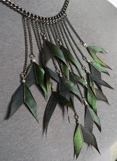Magpie Feather Necklace, These magpie tail feathers have been hand cut into arrowhead shapes and attached to various lengths of fine gunmetal chain. They're arranged asymmetrically in a group that's suggestive of a flock in flight.