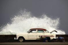 Un homme change les pneus de sa voiture, le long des quais de la Havane à Cuba, alors qu'une vague impressionnante passe par-dessus la jetée le 7 novembre 2011.  Image: Reuters