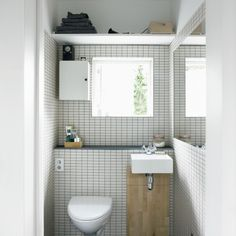 How much bigger would our tiny bathroom feel with a wall-mounted toilet and sink? Small whte Danish bathroom from Bolig Magazine;