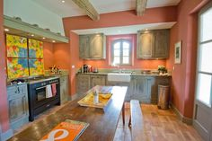 Provençal Farmhouse style kitchen with units distressed to match the ceiling beams and a warm colour scheme.