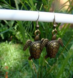 These are brass color metal charm earrings of sea turtles.  Very cute earrings for the fun side.