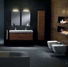 Cette salle de bain moderne est composée de meubles en bois qui constrastent avec le sol foncé en béton ciré