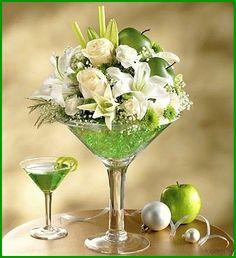 Grünes Glas mit weißen Rosen