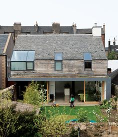 Konishi Gaffney residence - Edinburgh. The framed aluminum of the corner window by Natralight breaks up the roof of recycled slate tiles, which is entirely of a piece with the roofs around it. The Scottish oak cladding comes from Abbey Timber and the black aluminum cladding from MSP Scotland.