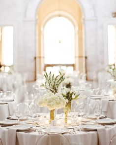 """Tables were set with centerpieces of hydrangeas, lilies of the valley, tulips, and snapdragons, and surrounded by transparent """"Mirage"""" ghost chairs."""