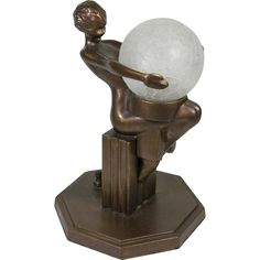 This lamp was sold under the name Frankart in the 1930s and has its' original bronze finish. A nude sits on a fluted column staring into a round globe