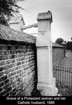 """""""'Til death do us part"""" - and even that couldn't separate this couple. the church would not let them be buried together. so they had this tombstone made to reach over the wall that separate them"""
