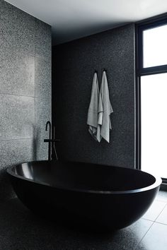 One stand-out feature in this modern master bathroom is the oval-shaped black freestanding bathtub. One stand-out feature in this modern master bathroom is the oval-shaped black freestanding bathtub. Chiaroscuro, Melbourne, Timber Staircase, Timber Battens, Dark Interiors, Design Language, Master Bathroom, Bathroom Black, Cozy Bathroom