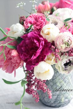 The guest book table will feature a white compote vase filled with hot pink hydrangeas, hot pink stock flowers, pink waxflowers, gilded leaves, light pink peonies, and Queen Ann's lace.