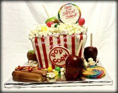 A great way to welcome fall, with an all edible carnival themed cake! The popcorn bucket is created from five layers of cake, hand carved and covered with fondant, the popcorn is made from marshmallows, the caramel and candy apples are just that, the hot dog is made from fondant, and there's candy and gum balls to complete this all edible sweet creation! #ejssweets #customcakes #cakesinmcdonough #carnivalcake #popcorncake