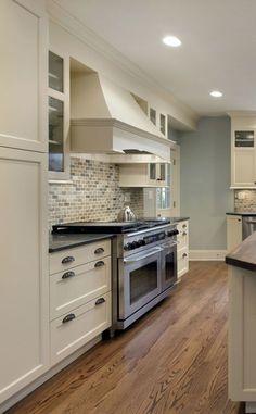 "Transitional kitchen.  Off white with large range hood, black granite countertop, brick pattern backsplash, 48"" range.  www.prasadakitchens.com"