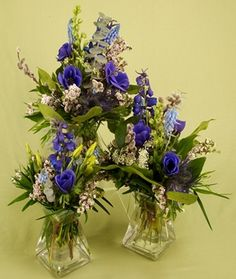 These pretty centerpieces are made of delphinium, anemone, spiral eucalyptus,  pussy willow, wax flower, grape hyacinth, lisianthus, salal and podocarpus. http://rebeccasflowershoppe.com/