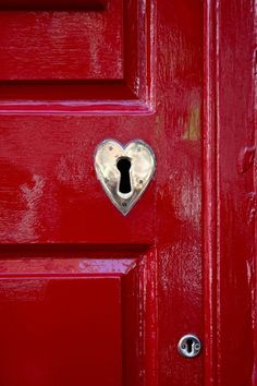 Red door with a silver heart keyhole.