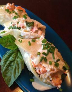 image of salmon stuffed shells drizzled with lemon cream sauce and garnished wih chives and a sprig of basil