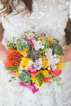 Vibrant orange, yellow and pink with succulents for this Mexican inspired bridal bouquet by Cabo Floral Studio. Photography by: www.pinkpalmmexico.com