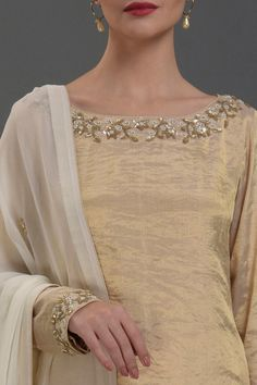 From our Wedding and Bridal Collection, this is an exquisite handwoven Banarasi Gold pure tissue boat neck top adorned with pearl beads, sequin and zardozi hand embroidery around front-back neckline and sleeve ends, and paired with ivory Chikankari-Kam Silk Kurti Designs, Churidar Designs, Kurta Designs Women, Kurti Designs Party Wear, Dress Neck Designs, Designs For Dresses, Bridal Blouse Designs, Kurti Embroidery Design, Embroidery Fashion