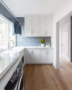 Amazing white laundry room renovation with grey blue tile backsplash. Modern laundry room, tons of space. White Laundry Rooms, Mudroom Laundry Room, Laundry Room Island, Blue Backsplash, Kitchen Backsplash, Laundry Room Design, Kitchen Design, Kitchen Ideas, Kitchen Reno