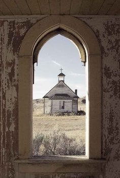 Through the vestibule window in the abandoned United Church in Dorothy, Alberta, looking out on the old Catholic Church at the end of a grassed-over dirt road.