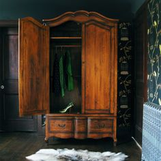 """With two hanging rails for displaying your designer dresses, and one large drawer for stashing away those more """"comfortable"""" pieces of clothing, the Dad's Antique Wardrobe is hand-carved and pre-aged, and, coupled with details such as the brass handles and faux keyholes, the piece has a truly enchanting, vintage feel."""