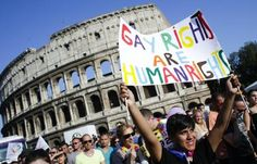EXPAND A woman holds a banner in front of the Colosseum during the annual gay pride parade in Rome on June 15, 2013.