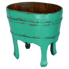 Perfect for potting fresh blooms or stowing garden tools, this handmade wood planter showcases a lovely turquoise hue and weathered finish.