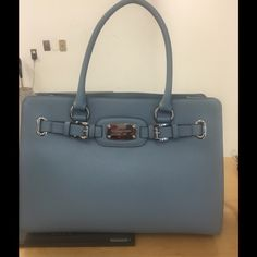 Authentic Michael Kors Hamilton Light Blue Bag This Michael Kors handbag was purchased from a major retailer.  I can provide receipt.  A beautiful sea surf light blue leather, brand new with tags handbag.  A medium/large handbag.  Roomy strap over closure with chain/leather strap for costs body wear.  Shoulder strap is not detachable.  This is a very hard to find and purchase color! Michael Kors Bags Crossbody Bags