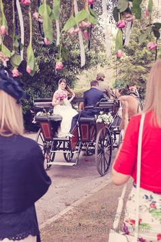 Newlyweds leave on horse drawn carriage. Photography by one thousand words wedding photographers