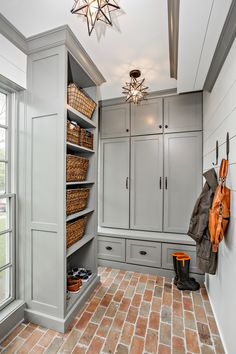 Mudroom with boarding on walls and enclosed cabinet storage.