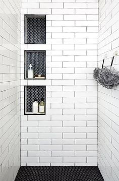 Triple stacked shower niches with black hexagon tiles surround long white shower tiles with black grout creating a unique and stylish walk-in shower design. 28 Inspirational Walk in Shower Tile Ideas for a Joyful Showering Black Hexagon Tile, Hexagon Tiles, White Tiles Black Grout, Hex Tile, Honeycomb Tile, White Shower, Small Tile Shower, Shower Accent Tile, Tile Shower Shelf