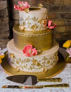 Stunning White & Gold Wedding Cake with our matching Venice Gold Cake Server Set (Wedding Star 8699) | Buy at Wedding Favors Unlimited (http://www.weddingfavorsunlimited.com/venice_gold_cake_serving_set.html).