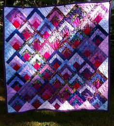 SOLD-#1 OF 3  Quilted quarter log cabin squares on point. Using purples and a ruby center. 54x54 Jenn-Alabama.