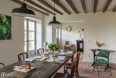 Chez Marie du Sordet, table à manger réalisée avec de grandes planches de bois de récupération, chaises de bistrot, suspensions émaillées d'usine