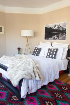 Kelli Ryder Home Tour -- I need that tripod lamp. Black and white art over the bed.