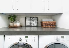White and gray laundry room boasts a white front load washer and dryer tucked under a gray countertop alongside a dove gray subway tiled backsplash under white flat front cabinets.