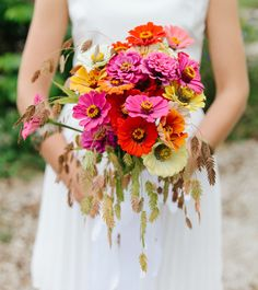 ZINNIA: This flower's defined petals create a whimsical feel; it's typically available in bright orange, red, and pink. When mixed with a few rustic accents, it creates a stylish combination like this amazing deconstructed bouquet.