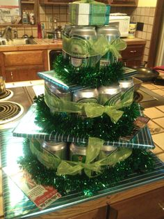 Birthday gift for him!!  Super easy to do!! 24 pack of Heineken, garland and the tiers are only plywood covered with wrapping paper! Theres other gifts inside the circles of beer!  Gave gift cards to places he likes.  Barber, car wash, Dunkin and places to eat. Outlined with scratch tickets!