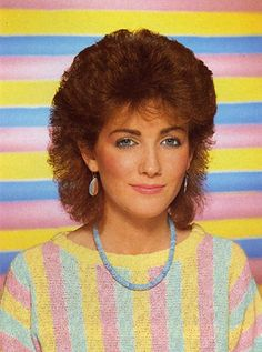 Hairdo Don't of the 80's. Check out the alternating pattern of her top and the background. Very clever the set designers were. Stylin!