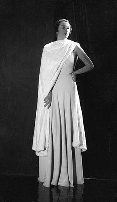 Photographie de Madeleine Vionnet, grande couturière française, née à Chilleurs-aux-Bois le 22 juin 1876 et décédée à Paris le 2 mars 1975. Elle a eu une influence majeure de la mode du XXᵉ siècle. Son vêtement fait référence aux drapés Grecque.