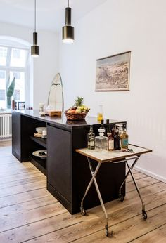 Kitchen island with industrial pendants and a rolling bar.
