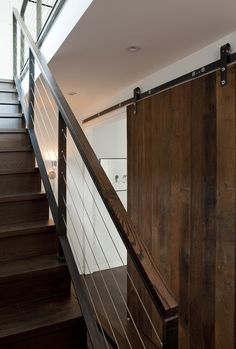 "Two upper floors of Brooklyn townhouse. The stairs between the second and third floors are more solid and built-in. In the private realm on the second floor, a sliding barn door closes off the rooms from visibility and noise. ""The barn door slides with ease because of the heavy-duty hardware we selected,"" says Khanna."