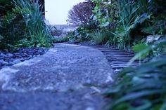 株式会社都田建設ドロフィーズの敷地内にある蔵BookStore奥の隠れ庭。 蔵のリノベーション時から残っていた屋根瓦をアプローチ脇に、小さい玉砂利と組み合わせてデザインした和庭園です。