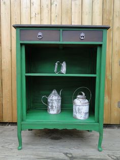 This used to be a cabinet, but with the doors removed it is an open shelf ready for books or baskets or anything in between. It's been painted a bold green that has been toned down a bit with the dark stained top and drawers. Dressed up with a tiny bit of fancy on the original pulls. Modern Vintage