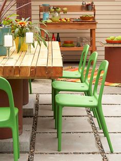 rustic table with bright plastic chairs on a patio made of large pavers. #yard #backyard #patio