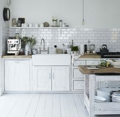 white on white kitchen with natural timber benchtops. loving the island chopping block, subway tiles and painted floors.