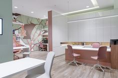 A large digital print inspired by nature has become the main stimulus of the color choices. White -vertical and horizontal- surfaces diffuse smoothly the lighting, while shades of pink gold and green match harmonically with the wooden choices on the floor and on the desks' details. Both for visitors and employees, has been created a metaphorical escape through the leafy background and the large windows. Side Door, Create Space, Large Windows, Pink And Gold, Diffuser, Blinds, Digital Prints, Shades, Flooring