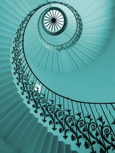 Walking up a teal spiral staircase