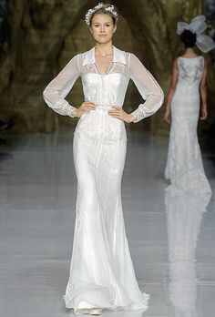 "Brides.com: Pronovias - Spring 2014. ""Yelimar"" lace and organza sheath wedding dress with sheer long sleeves and a collar neckline, Pronovias"