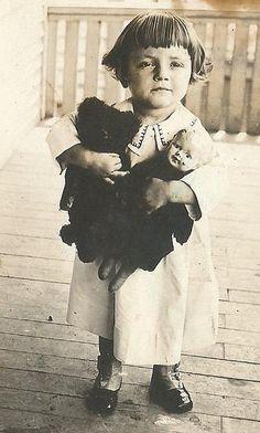 A little girl with a teddy bear and doll.