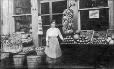 italians migrants in Pennsylvania - black and white photo standing in front of store, bins of vegetables and fruits on both sides along the sidewalk - many immigrants opened stores that provided people of their ethnic group with foods they were familiar with from the Old Country.